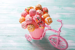 Bright cake pops  in decorative bicycle on turquoise  wooden bac Stock Photos