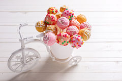 Bright cake pops  in decorative bicycle on white wooden backgrou Stock Image