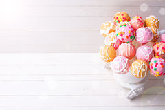Bright cake pops in ray of light   on white wooden background. Stock Image