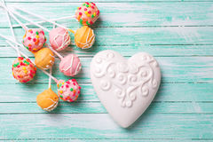 Bright cake pops  and white heart on turquoise  painted wooden b Royalty Free Stock Photos