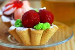 Bright cakes in the form of baskets on the background of a wooden table with tea. Two bright cream cakes in the form of baskets on the background of a wooden Stock Images