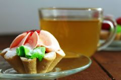 Bright cakes in the form of baskets on the background of a wooden table with tea. Two bright cream cakes in the form of baskets on the background of a wooden Stock Photo