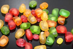 Bright candy caramel and marmalades scattered on a dark background. Many multicolored sweet candies. Close-up stock photo