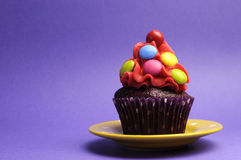 Bright candy covered cupcake on purple background - horizontal. Stock Image