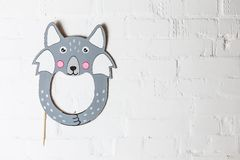 Bright cardboard mask on a white brick wall. royalty free stock photos