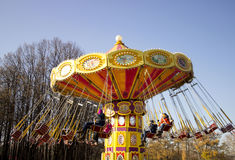 Bright carousel with chains spinning around in the park with the children.Motion blur. Stock Photos