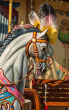 Bright carousel in a holiday park. Horses on a traditional fairground vintage carousel. Stock Photos