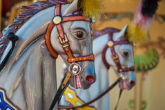 Bright carousel in a holiday park. Horses on a traditional fairground vintage carousel. Royalty Free Stock Photography