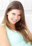 Bright caucasian woman looking at camera on a sofa Stock Image