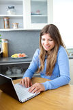Bright caucasian woman using her laptop at home Stock Images