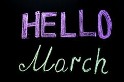 Bright chalk drawn text  `hello march`on blackboard. Bright chalk drawn text  `hello march` on blackboard Royalty Free Stock Image