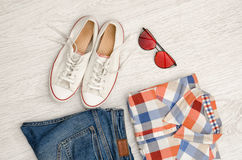 Bright checkered shirt, glasses, sneakers and jeans. Wooden background. Fashionable concept Stock Images