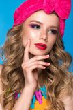 Bright cheerful girl in home hat, colorful make-up, curls and pink manicure. Beauty face. Bright cheerful girl in a home hat, colorful make-up, curls and pink royalty free stock photo