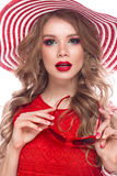 Bright cheerful girl in summer hat, colorful make-up, curls and pink manicure. Beauty face. Bright cheerful girl in a summer hat, colorful make-up, curls and Stock Images
