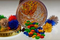 Party fun, chocolate treats spill out of a colourful container with bright, decorative pom poms stock photo