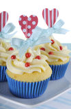 Bright and cheery red white and blue decorated cupcakes with heart toppers. And gift tag on vintage blue shabby chic background Stock Photography