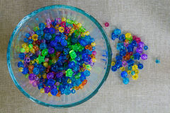 Bright children`s beads displayed in a bowl and scattered on a table Stock Photo
