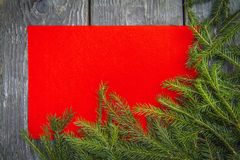 Bright christmas background with a copy space with fir branches with a wooden table and a red texture royalty free stock image