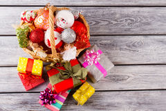 Bright Christmas balls and toy in a beautiful basket. Colorful Christmas presents are waiting for the new year. Cute New Year composition Royalty Free Stock Images