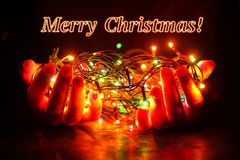Bright Christmas garland in the hands Stock Photography