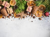 Bright Christmas or New Year background with thuja branches, Christmas decorations, spices, nuts, dried orange slices, pine cones. Copy space royalty free stock photography