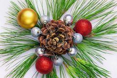 Bright Christmas ornament from pine sprigs, cone and Christmas b Stock Image