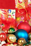 Bright Christmas Ornaments. Colorful Chrismas tree ornaments and presents focus on the foreground, blurred background Stock Photo