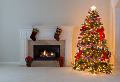 Bright Christmas tree with burning fireplace royalty free stock photography