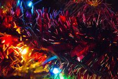 Bright Christmas tree lights and tinsel. Blue, yellow and green Christmas tree lights and tinsel Stock Images