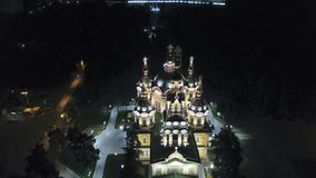 Bright Church with Golden domes and crosses. Glows in the night Park. Drone footage. Top and side view. Evening Cathedral in the Park. Bright temple. Modern royalty free stock photography