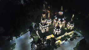 Bright Church with Golden domes and crosses. Glows in the night Park. Drone footage. Top and side view. Evening Cathedral in the Park. Bright temple. Modern stock photography