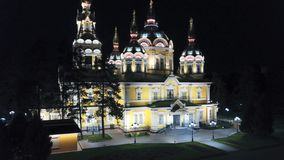 Bright Church with Golden domes and crosses. Glows in the night Park. Drone footage. Top and side view. Evening Cathedral in the Park. Bright temple. Modern royalty free stock images