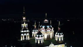 Bright Church with Golden domes and crosses. Glows in the night Park. Drone footage. Top and side view. Evening Cathedral in the Park. Bright temple. Modern royalty free stock image