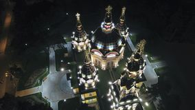 Bright Church with Golden domes and crosses. Glows in the night Park. Drone footage. Top and side view. Evening Cathedral in the Park. Bright temple. Modern stock images