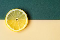 A bright circle of lemon on a yellow-green background. Stock Image