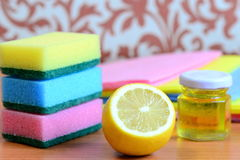 Bright cleaning sponge and rags set, olive oil in jar, lemon on a wooden table. Eco friendly house cleaning concept. Closeup Stock Photography