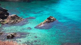 Bright and clear turquoise water with coral reefs and rocks. Stunning bright and clear turquoise water of Aegean sea with coral reefs and rocks washing by waves stock video footage