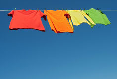 Bright clothes on a laundry line. And blue sky with copy space Stock Photos