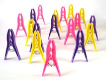 Bright clothes pegs standing on white background Royalty Free Stock Images