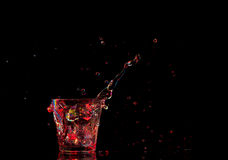 Bright cocktail in glass and splashing water on dark background Stock Image