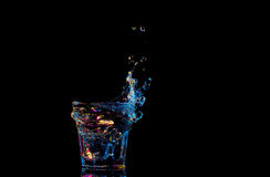 Bright cocktail in glass and splashing water on dark background Royalty Free Stock Photos