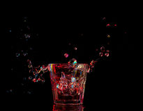 Bright cocktail in glass and splashing water on dark background Stock Images