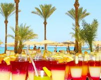 Bright cocktails in background of tropical resort with palm trees, sea and people. Holiday concept. Hurghada, Egypt 29 July 2018:Bright cocktails in background stock photos