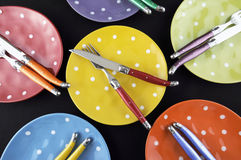 Bright color dinner party table setting. Dinner party table setting with red, blue, yellow, orange, green and purple bright polka dot plates and cutlery on Stock Image