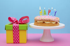 Bright color gift box with cake and candles. Royalty Free Stock Image