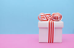 Bright color gift box on pink and blue background. Stock Photos