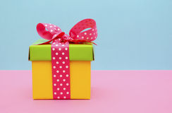 Bright color gift box on pink and blue background. Royalty Free Stock Photography