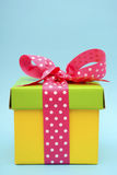 Bright color gift box on pink and blue background. Royalty Free Stock Images