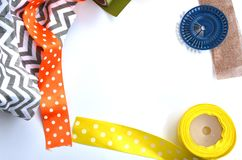 Bright color ribons and pins on white background, flat lay. Bright color yellow, orange, brown ribons and pins on white background, flat lay royalty free stock images