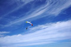 Bright color tandem canopy with two skydivers. Jumpers are flying and prepearing to landing stock image